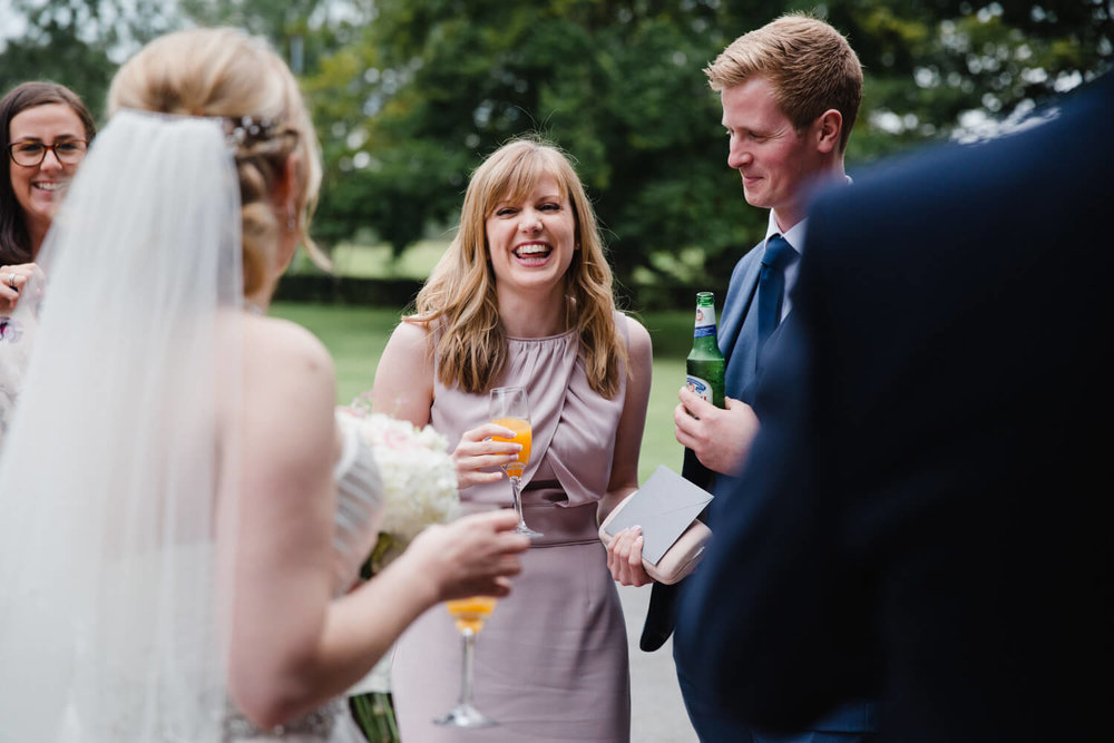 wedding guests laughing and joking with newly wedded couple