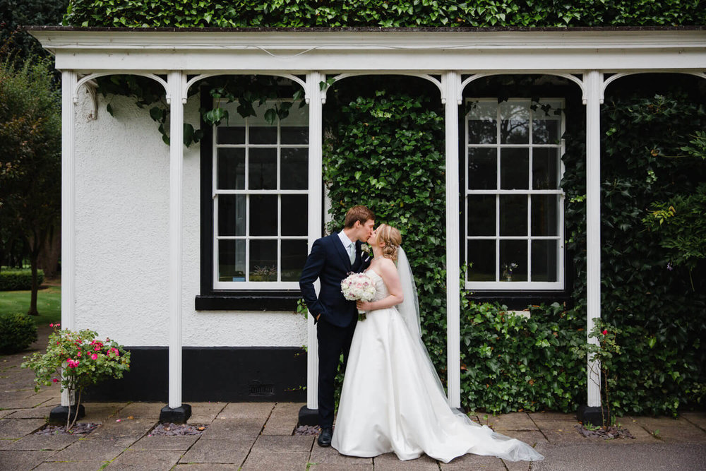 bride and groom wedding portrait in front of archways of statham lodge wedding venue