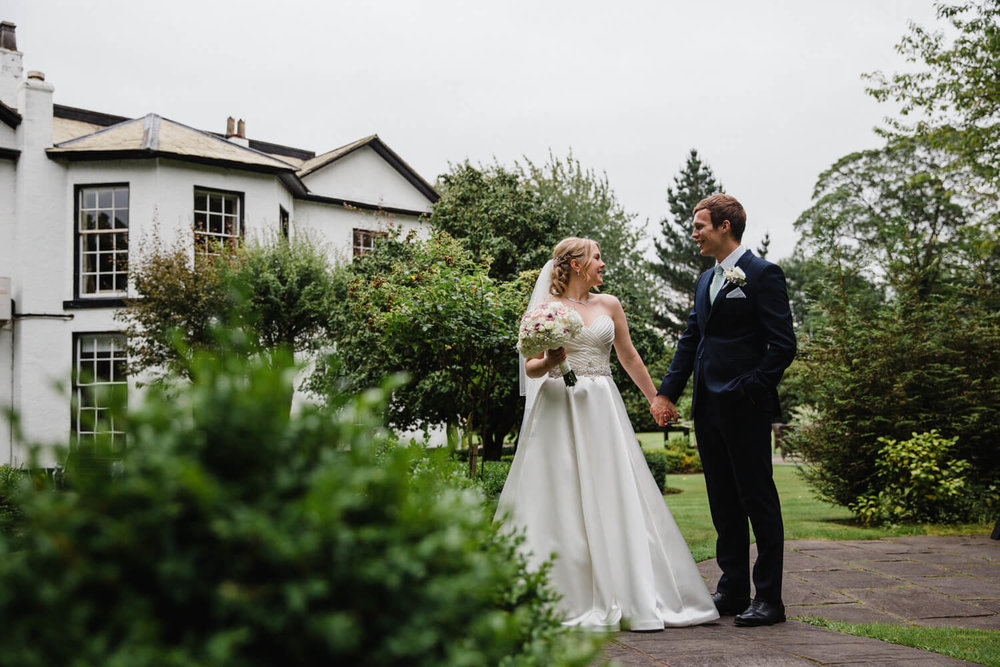 newlyweds holding hands on path with statham lodge in background