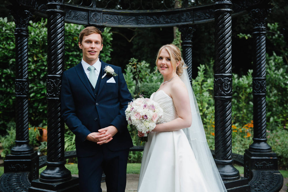 Groom leaning against gazebo pillar with bride holding bouquet and both looking into camera