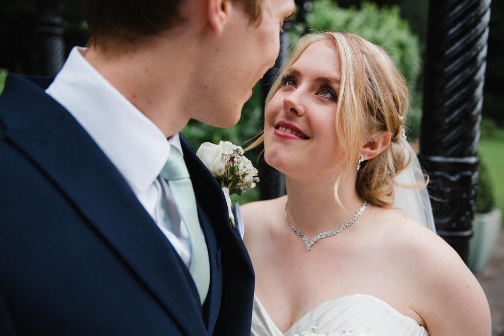 close up macro zoomed in photograph of brides eyes looking into groom in front of gazebo
