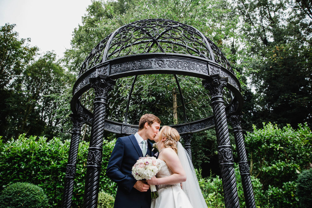 bride and groom kissing under gazebo in grounds of statham lodge