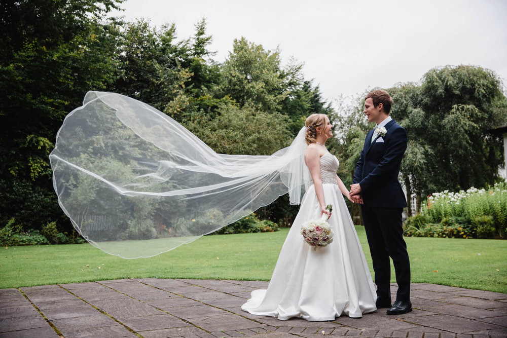 wide angle capture of bride and groom together in gardens and veil blown through the air