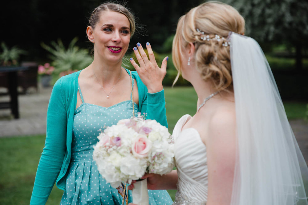 bridesmaid holding wedding ring while wiping away tear from eye