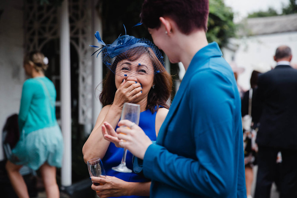 lady wedding guest in blue dress laughing with friend in garden