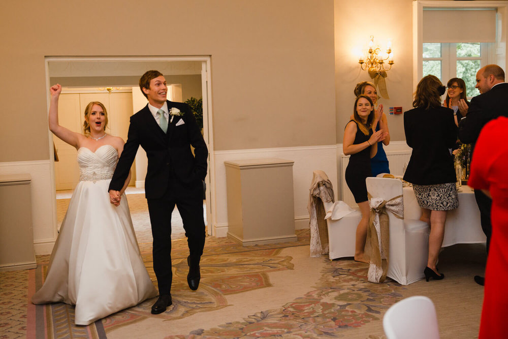 bride and groom entering into wedding breakfast room with friends and family congratulating them