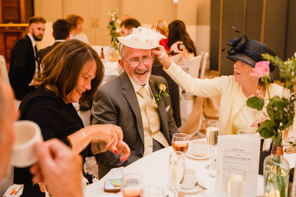 guest putting fascinator hat on uncle laughing at each other