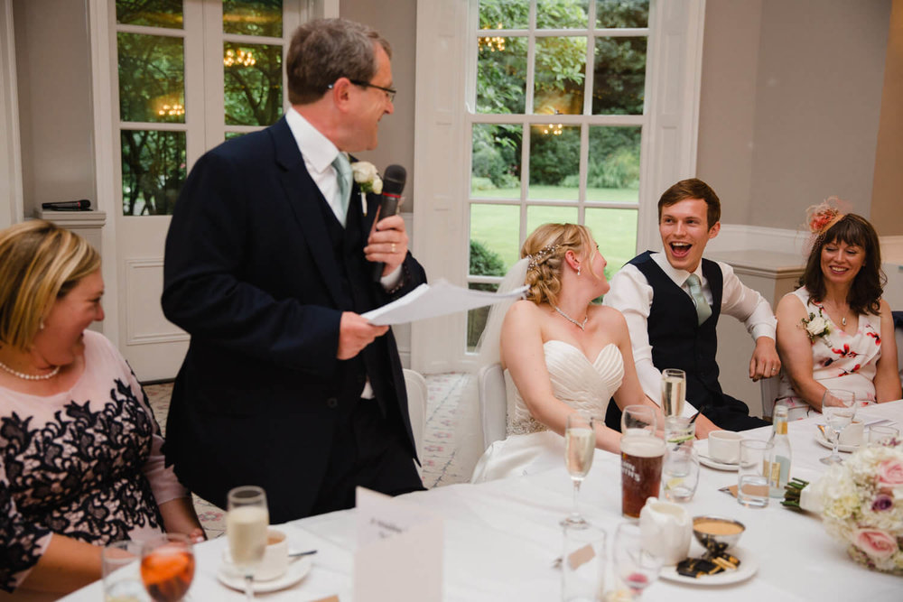 bride and groom laughing together at fathers speech