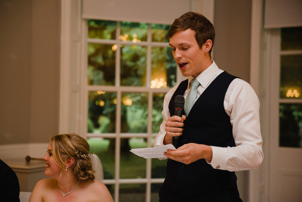 groom giving speech to wedding party