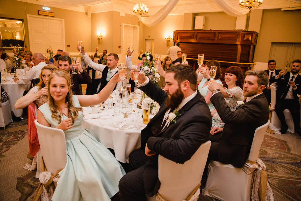 wedding guests raising a toast to newly wedded couple