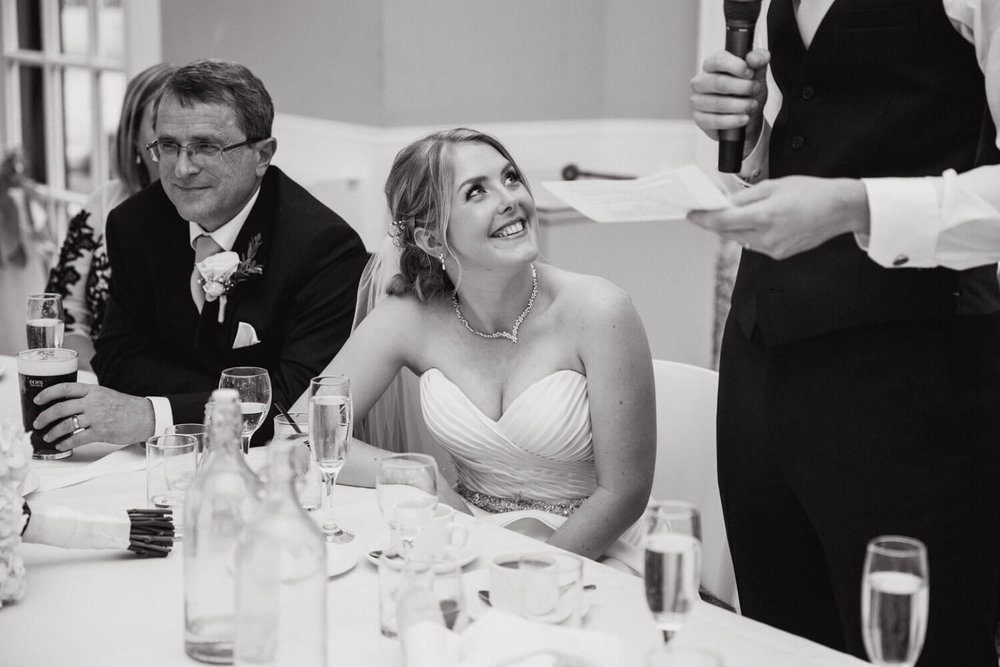 bride laughing and smiling at groom speech