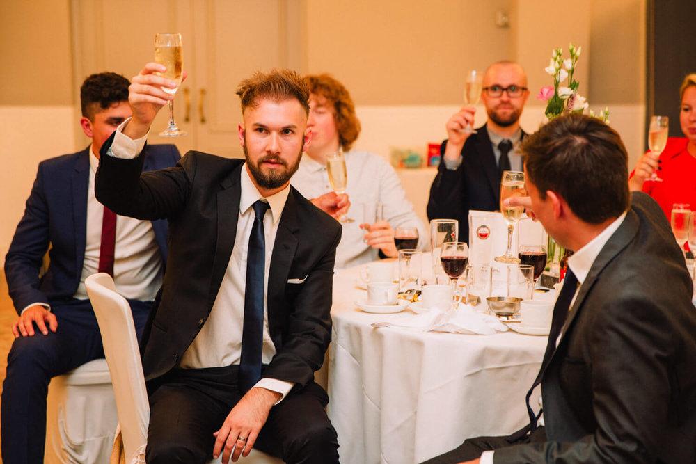 usher raising a glass to newlyweds
