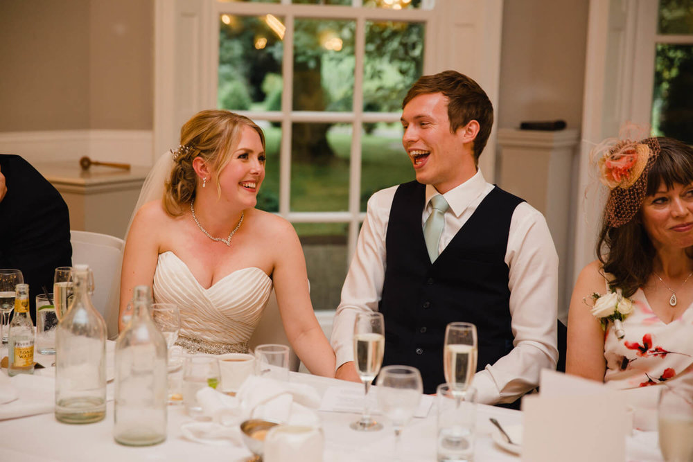 bride and groom laughing and joking loud on top table
