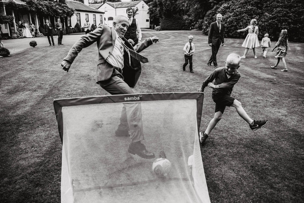 pageboy kicking football into goal