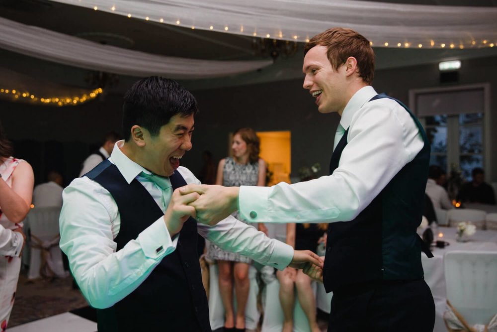 groom and best man dancing together at end of the night