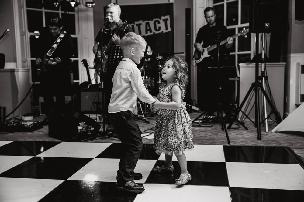 flower-girl and pageboy holding hands and dancing