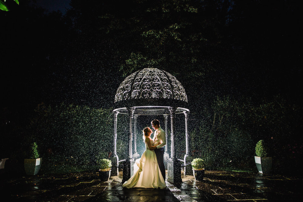 night time flash lit silhouette photograph of bride and groom in gardens under gazebo in the rain at Statham Lodge Wedding Venue