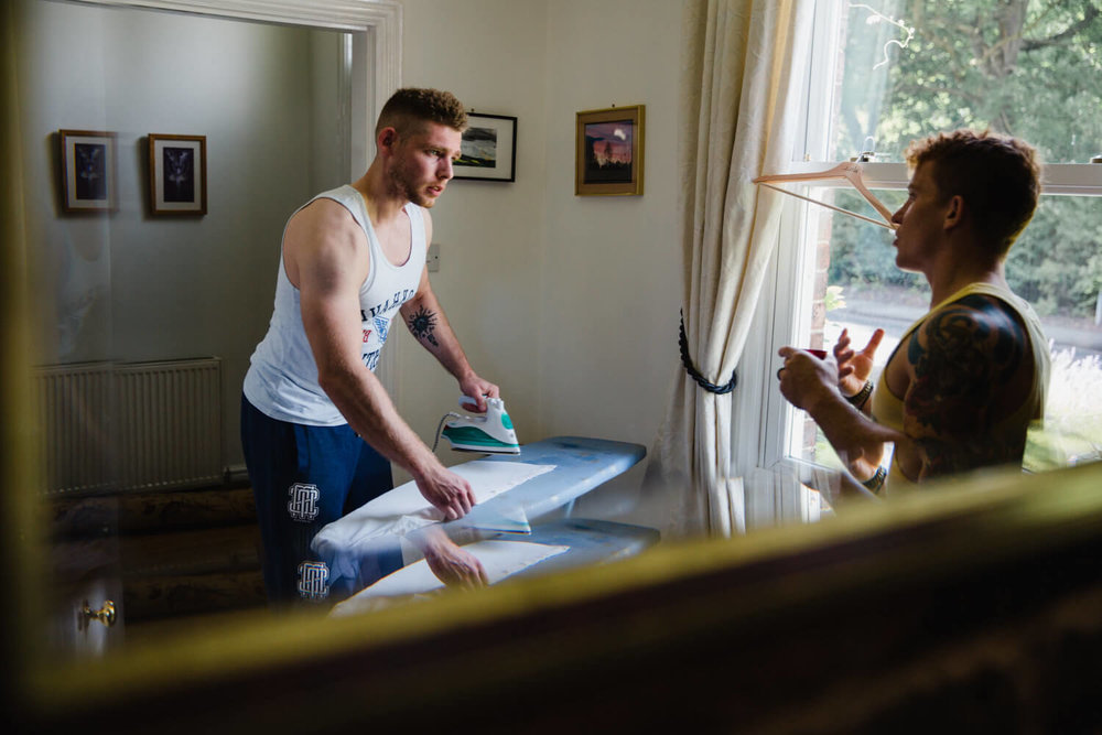 photograph of reflection in dining room of house with best man and usher ironing suit