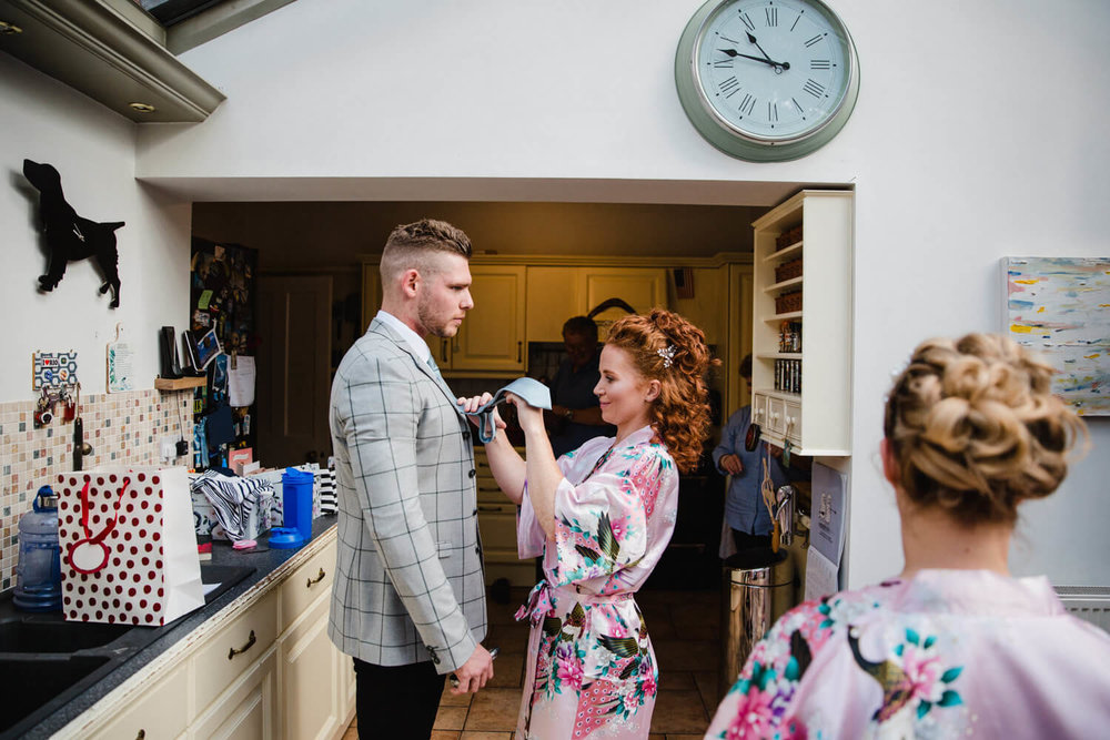 bridesmaid in dressing gown fixing groomsman tie in kitchen