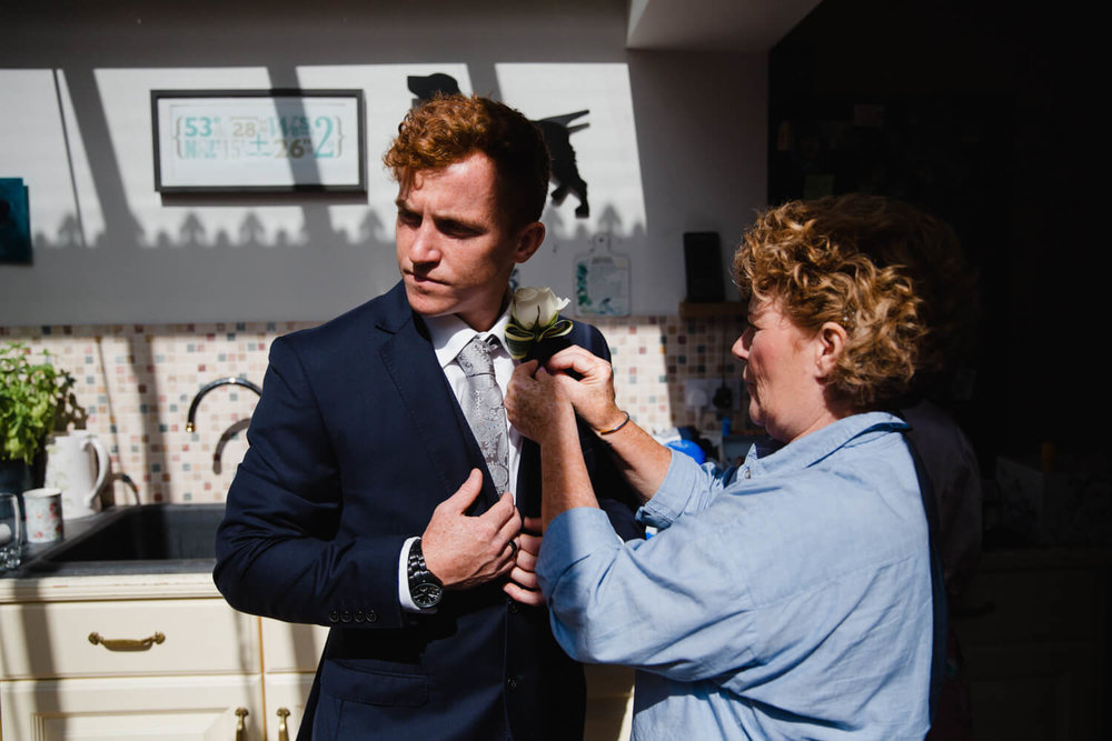 best man and brother fixing pin hole flower to lapel of suit jacket in kitchen