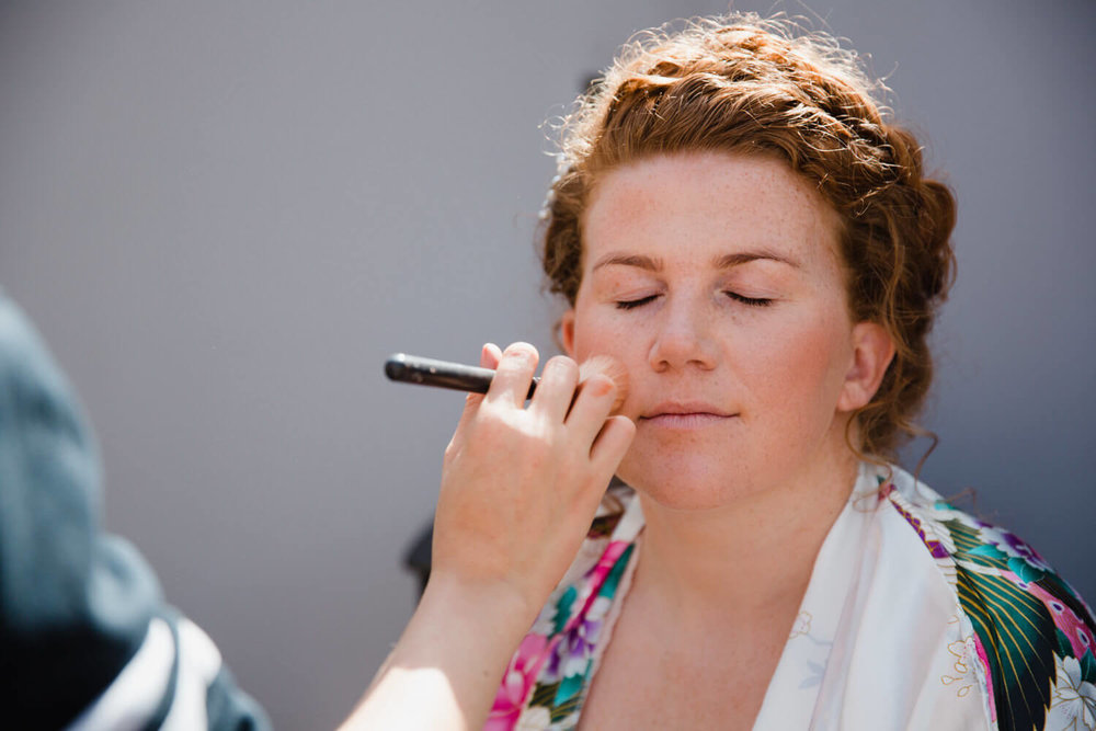 close up photograph of bride having make-up done
