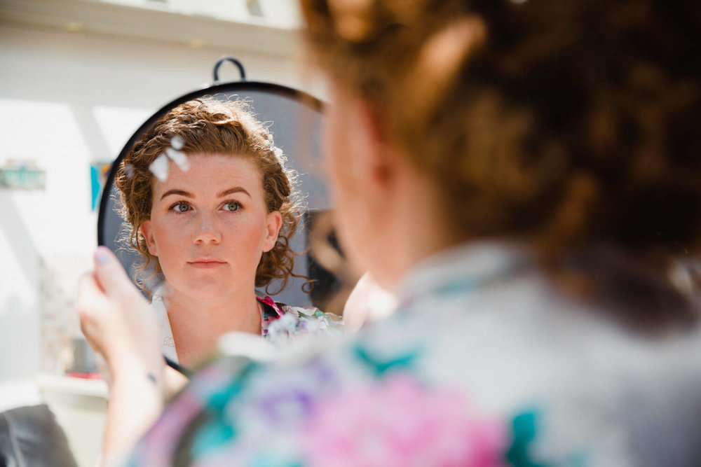 bride looking in mirror at make up preparation