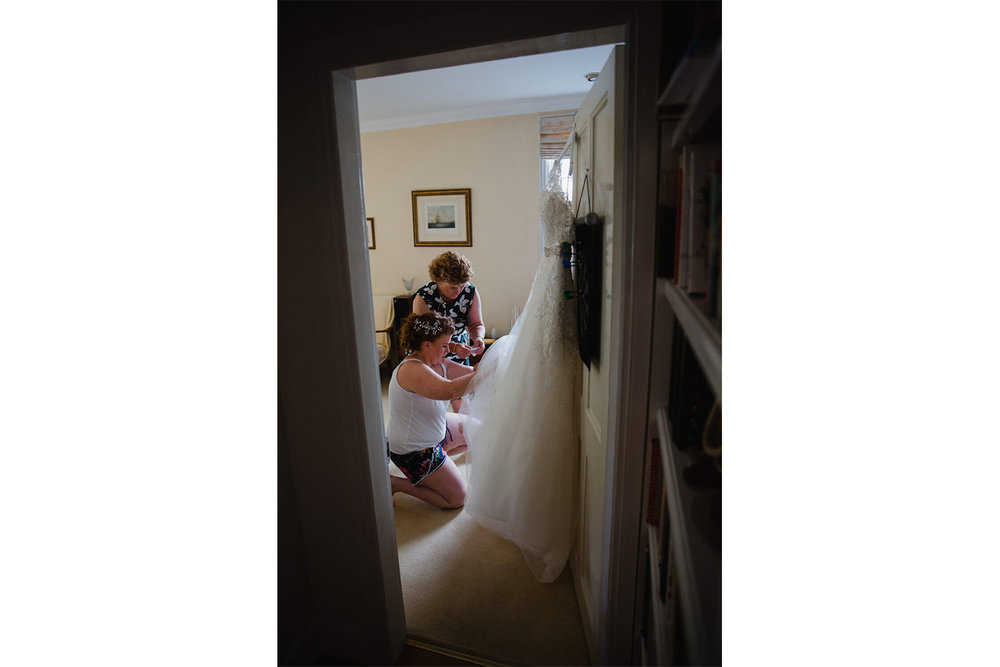 bride with mother tidying veil and wedding dress hung on door of living room