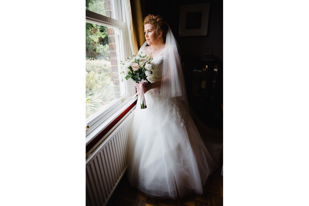 portrait of bride holding bouquet of flowers looking outside window