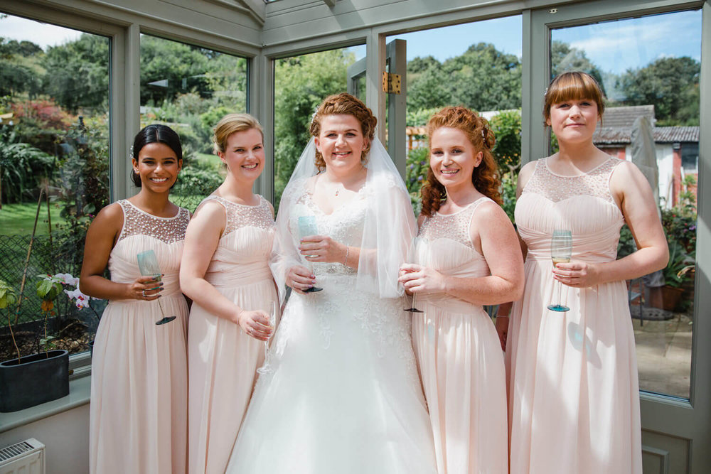 bride with bridesmaids holding champagne glasses for photograph together in conservatory