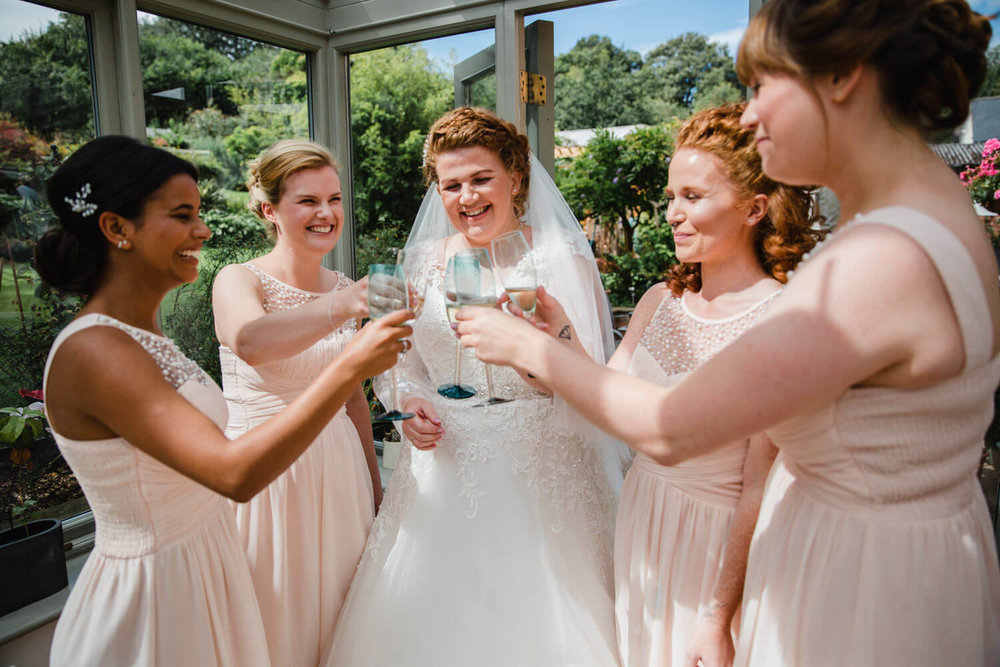 natural shot of bridal party clinking glasses in conservatory