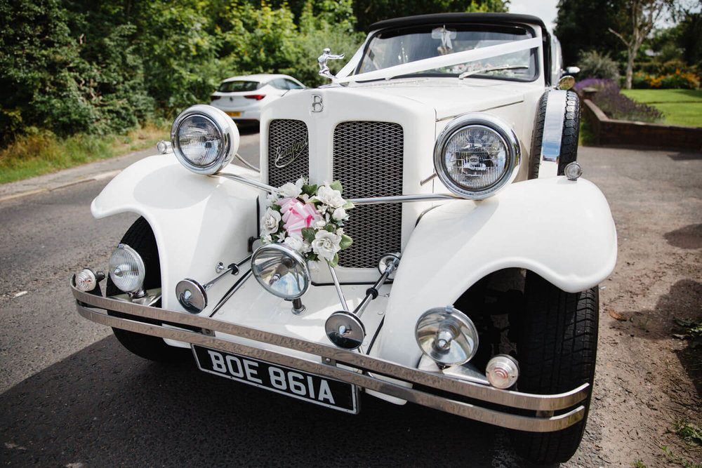 white old fashioned vintage wedding car parked up outside brides house