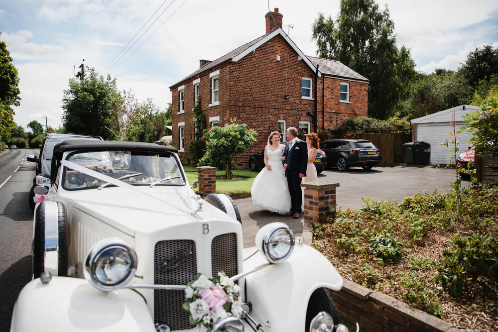 bride linking arms with father outside house while walking to the wedding car