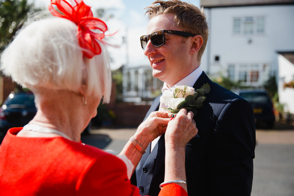 groom having pinhole flower attached to lapel of suit jacket