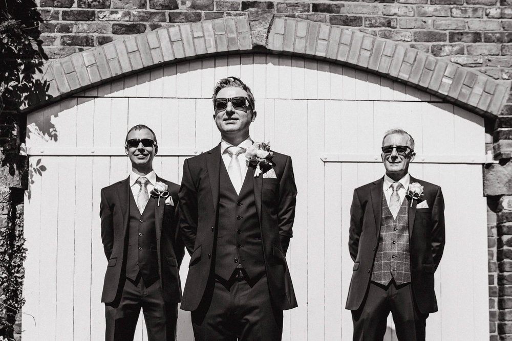 black and white photograph of groom and ushers wearing sunglasses
