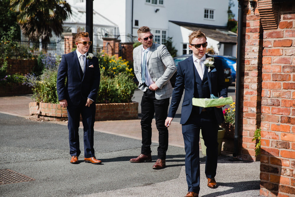groom carrying pinhole flowers while best man tucks in his shirt