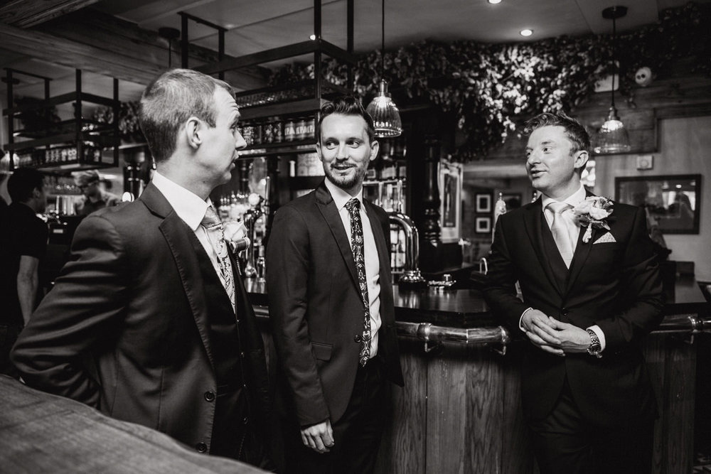 groom and friends at the bar ordering drinks