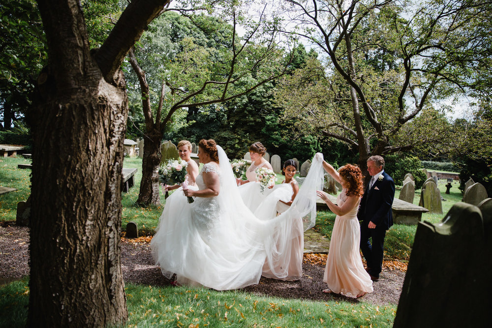 side view of bride and bridal party with bridesmaids carrying veil and helping with dress