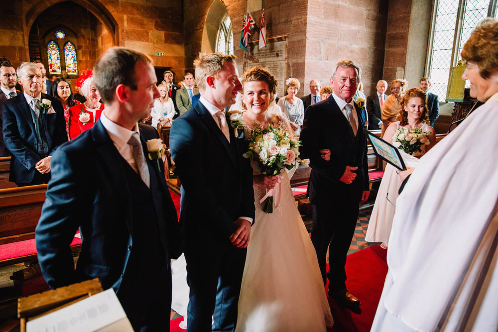 bride reaches top of aisle alongside groom as ceremony begins