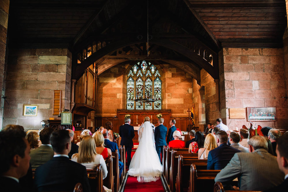 wide angle lens photograph of couple at front of church during service