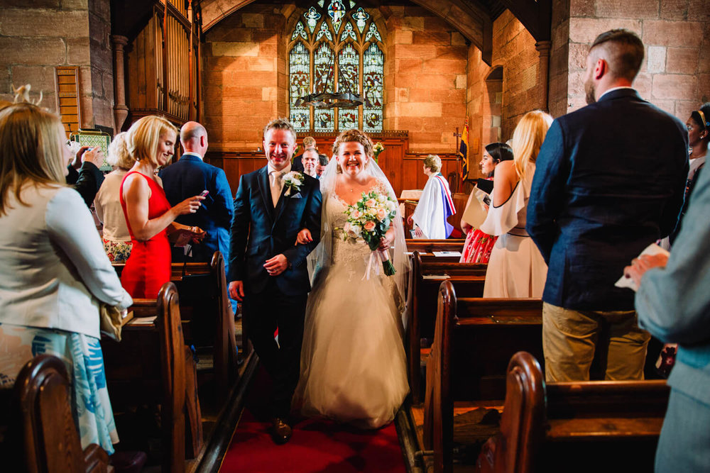 wide angle lens photograph of bride and groom walking down aisle at end of wedding ceremony