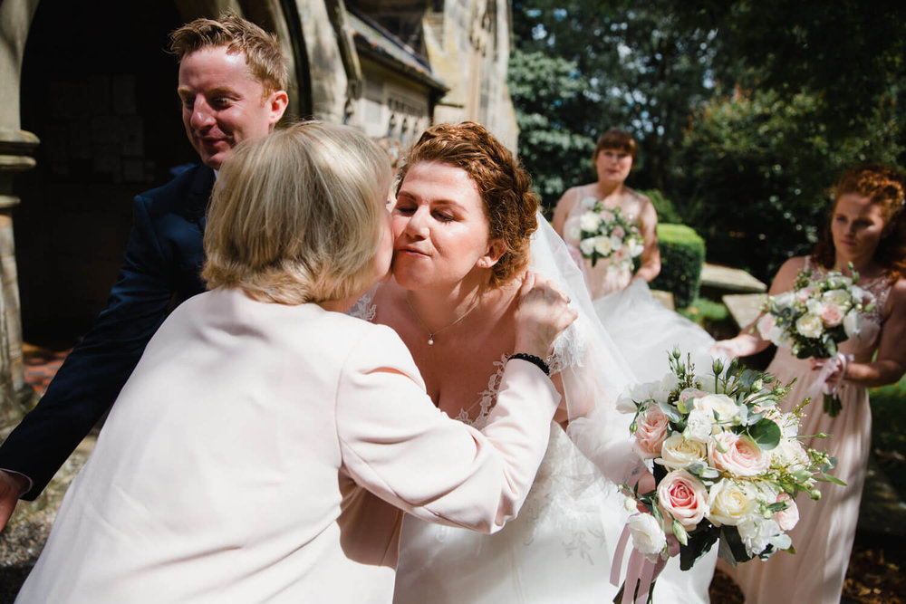 bride shares intimate kiss with mother outside church after service