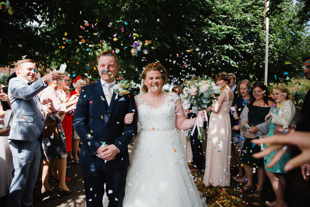 newlyweds having confetti thrown at them by wedding party