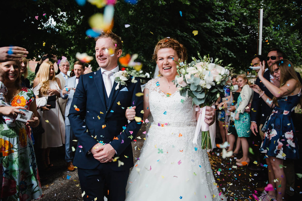 close up of bride and groom confetti shot outside church with friends and family