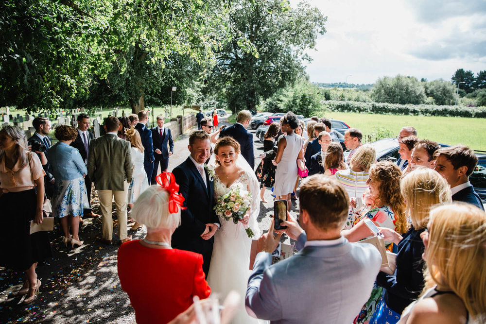 wide angle photograph of bride and groom surrounded by friends and family
