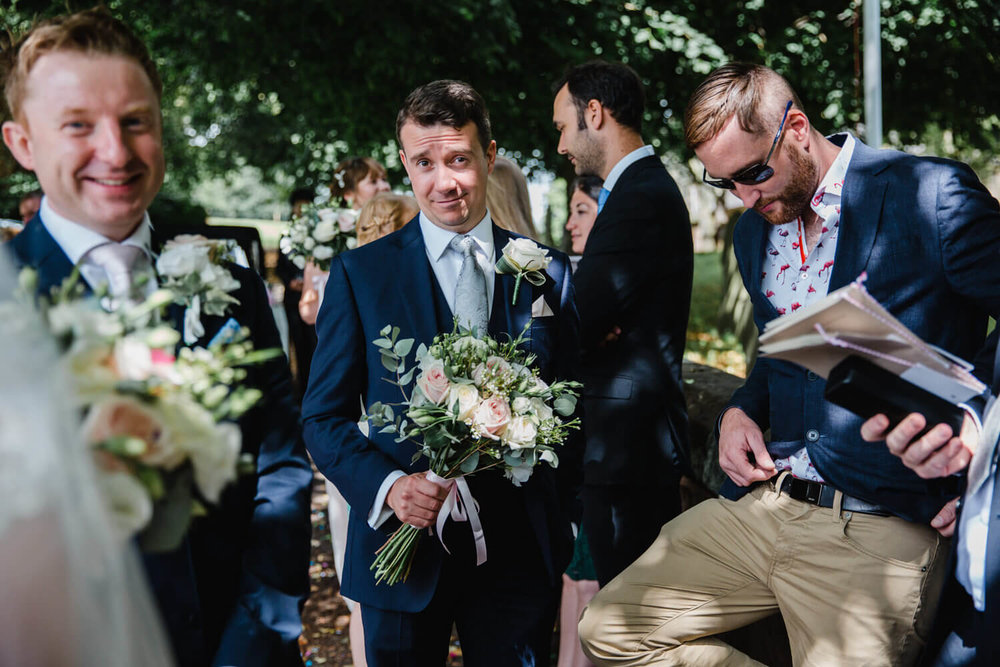 best man holding bouquet of flowers