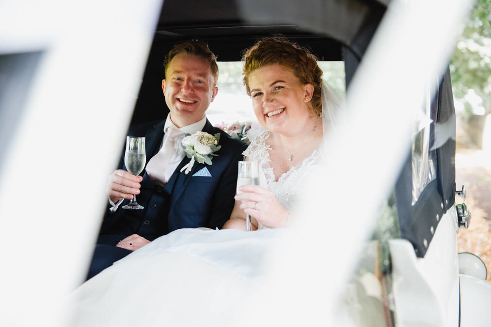 bride and groom clinking champagne glasses in vintage wedding car