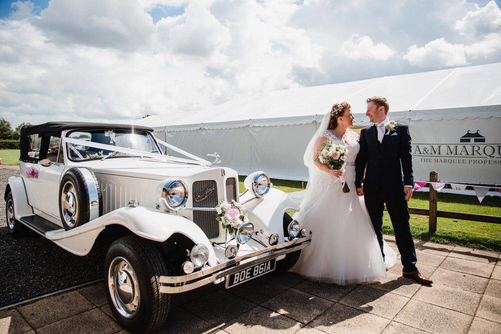 bride and groom holding hands alongside vintage wedding car in front of marquee