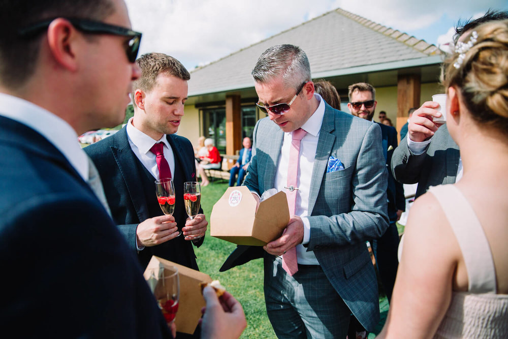 wedding guest eating from a food box