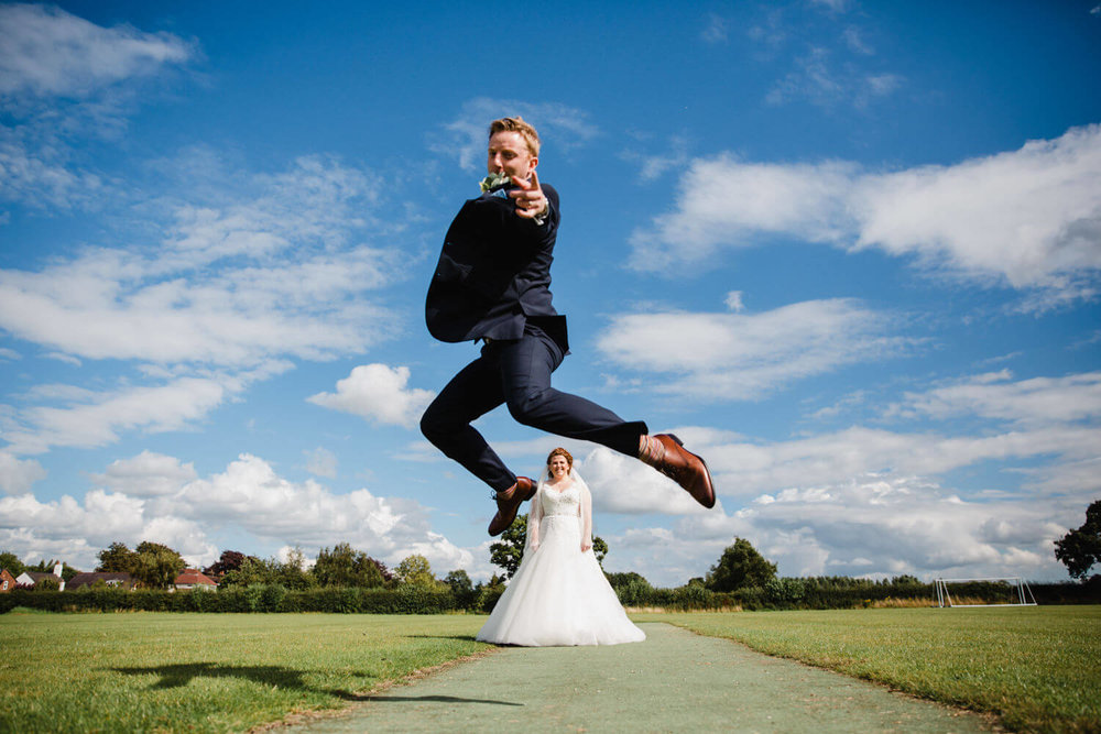 groom in foreground jumping over bride in background on the sports field