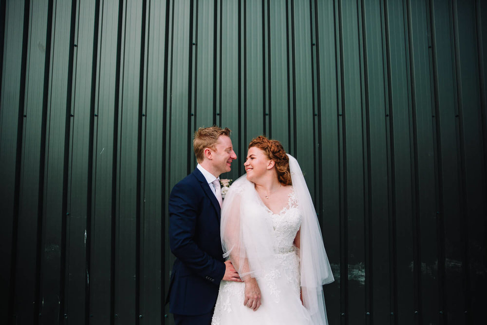 wide angle photograph of bride and groom in front of green metallic backdrop